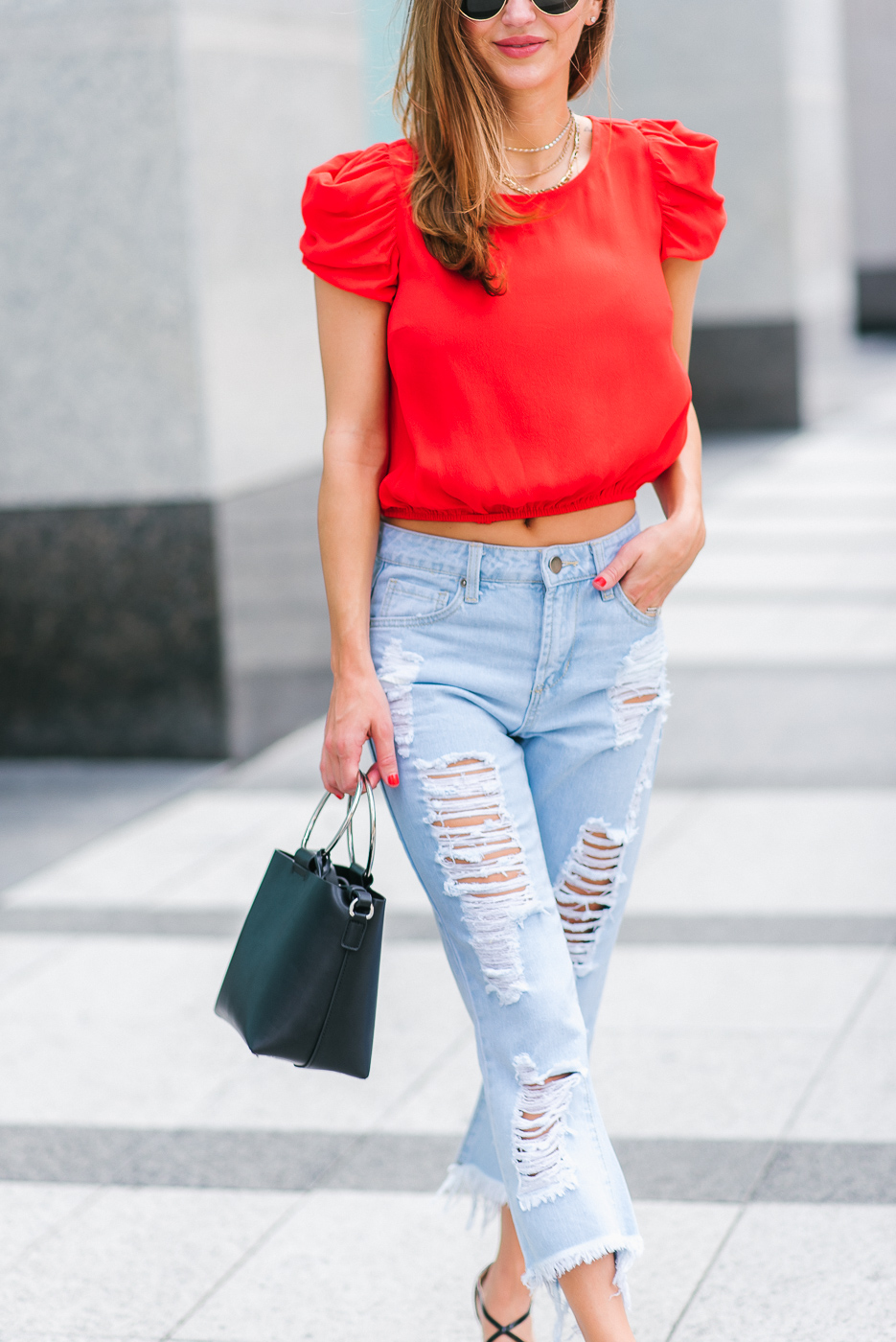 Street style fashion blogger in bright red top with capped ruffle sleeves
