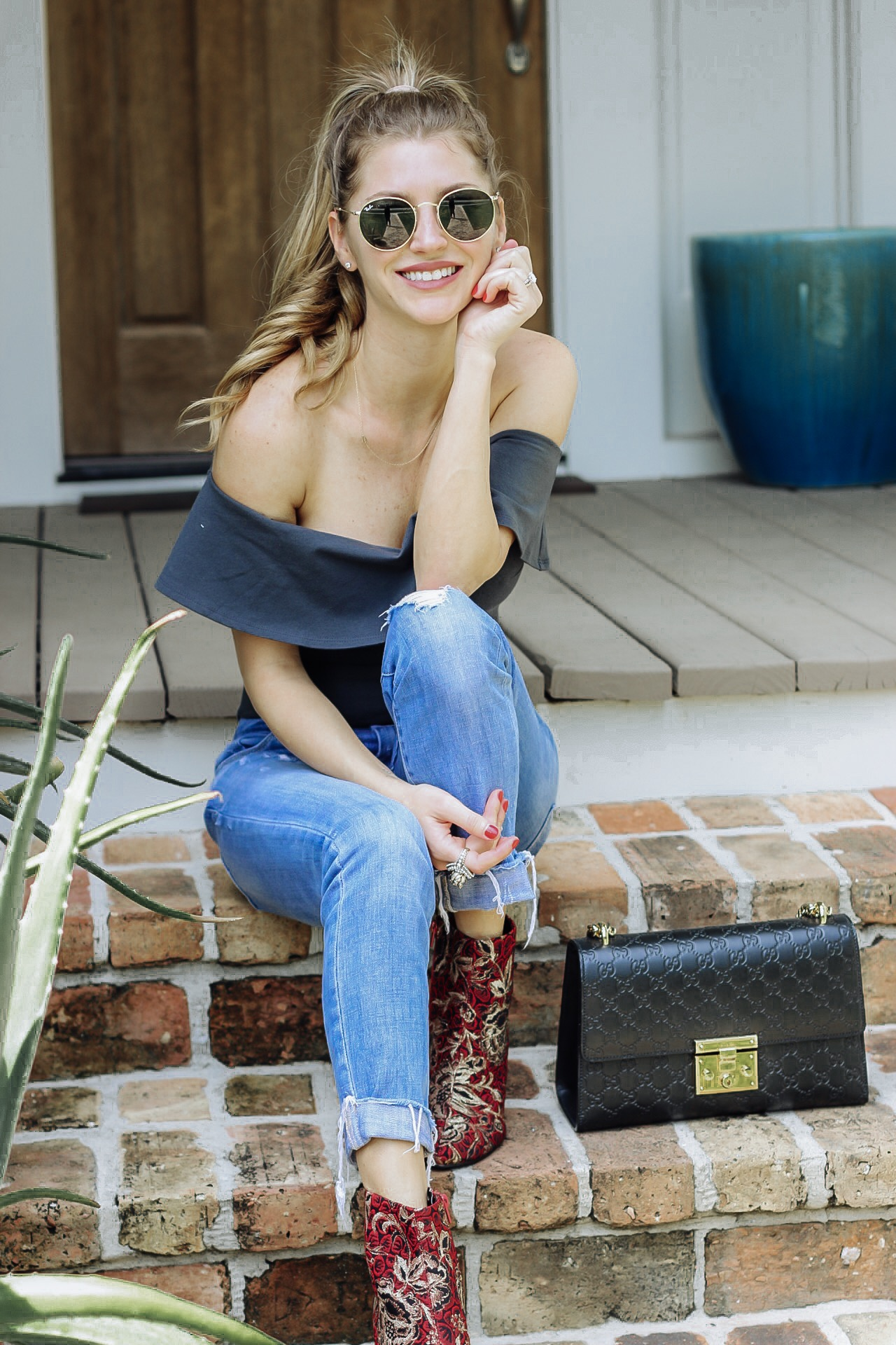 fashion blogger in off the shoulder top on front porch