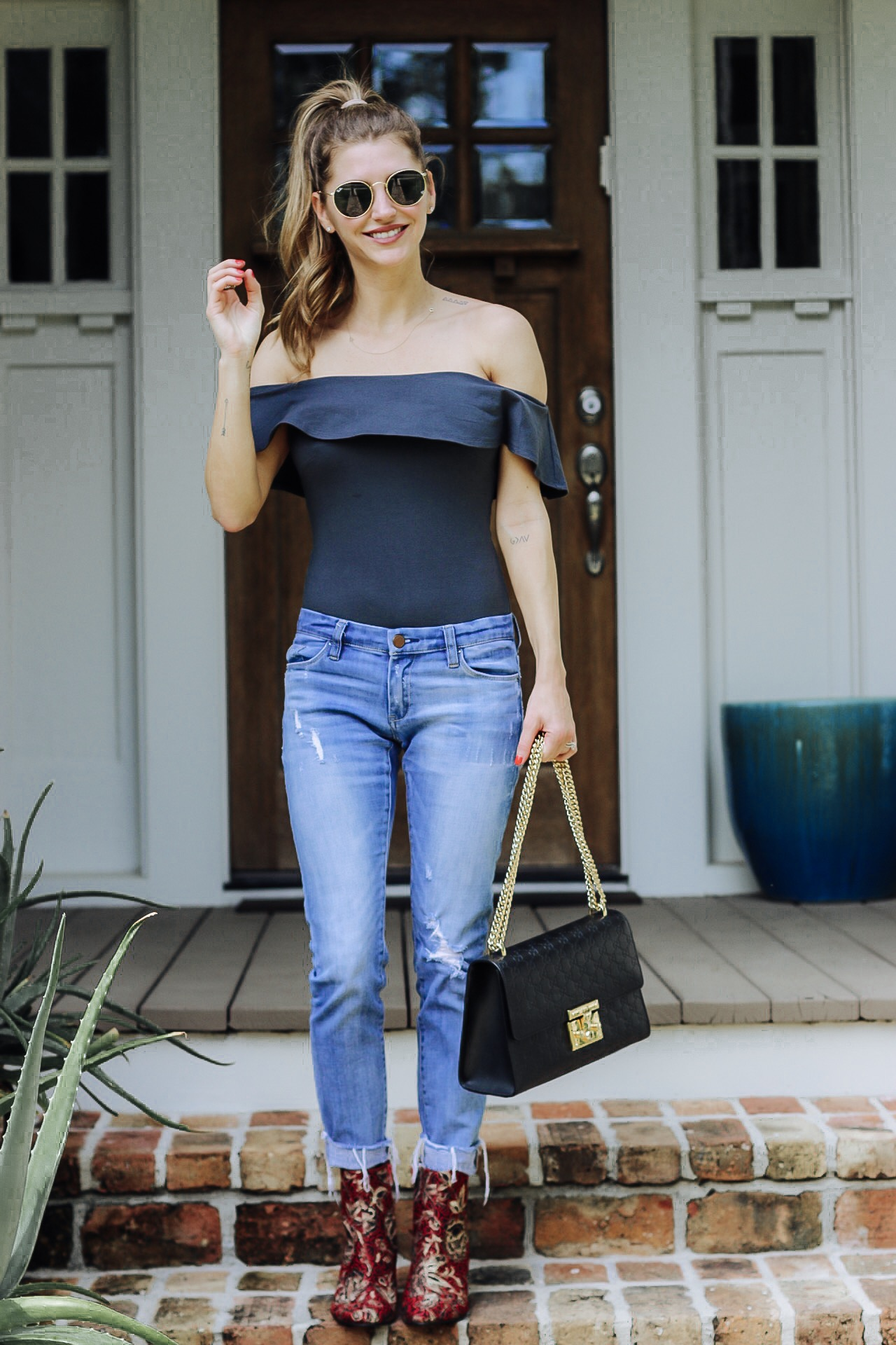 off the shoulder top with distressed jeans and Mark and Spencer boots