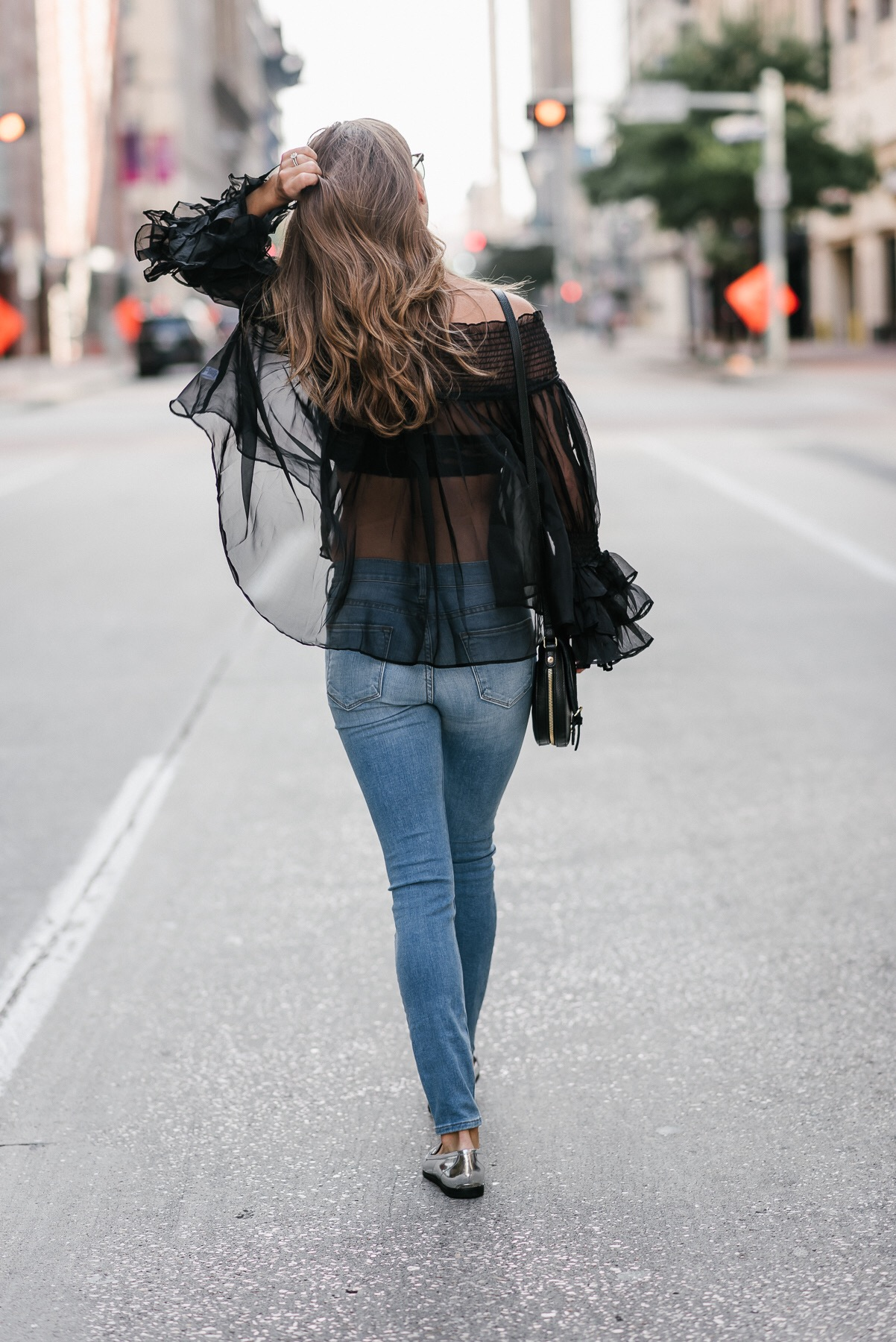 Showing the backsode of sheer top on fashion blogger and jeans from DSTLD