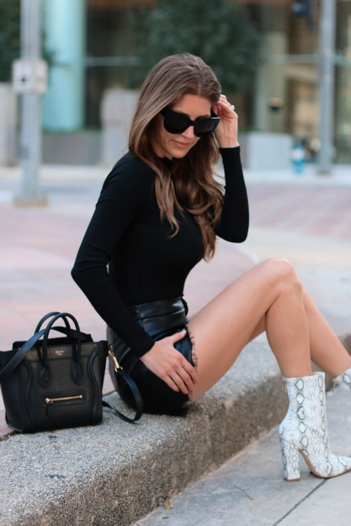 Leather bag with snake print shoes girl sitting on sidewalk