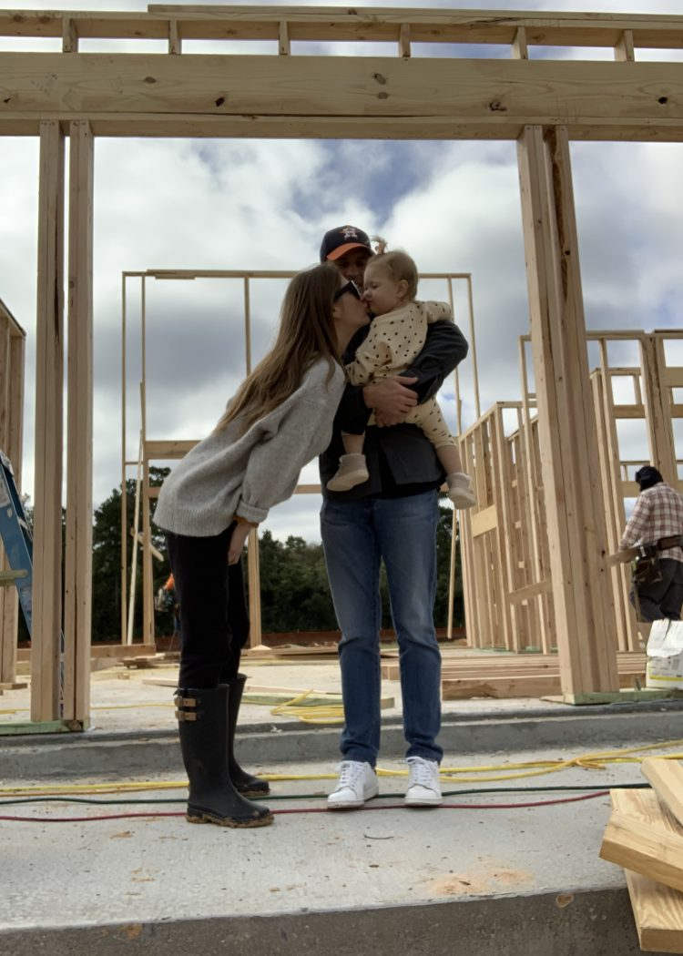 Arron, AshLee and Navy Williams standing in front of custom home with new frame.