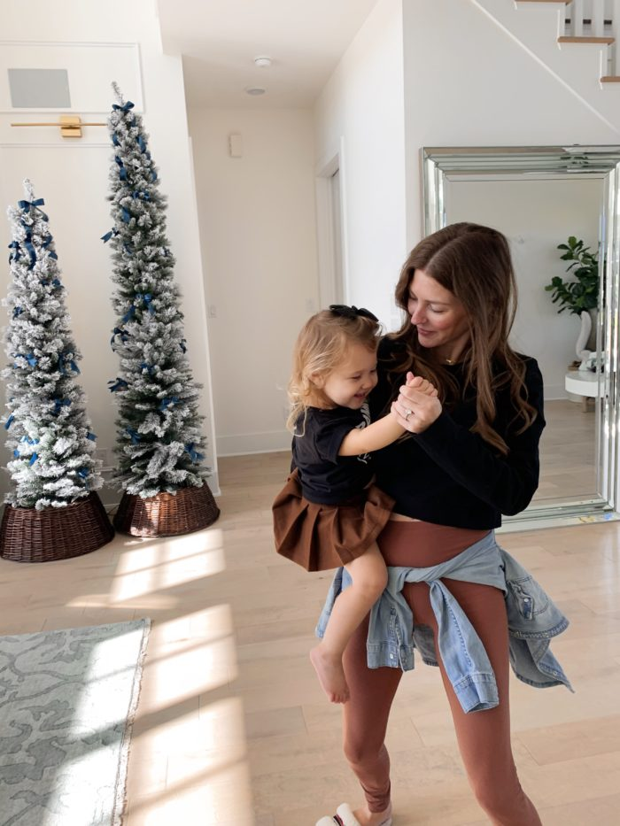 mommy and daughter dancing in matching black tops and brown skirt and pants